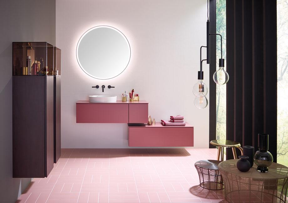 Deux meubles supsandus rose franboise sont surmonté d'un miroir rond génat pour une salle de basin à la fois futuriste et délicate.