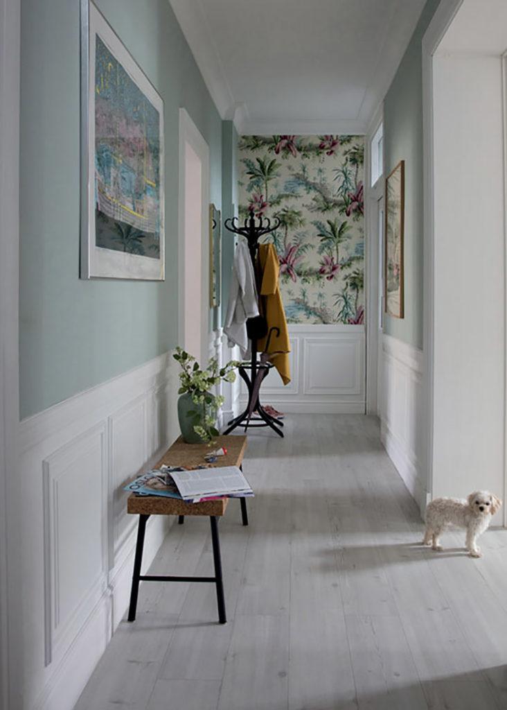 Le couloir d'une maison, joliment décoré d'un parquet gris au sol. Les murs sont peints en bleu céladon ou recouvert d'un papier peint fleuri. Un petit chien regarde l'objectif.