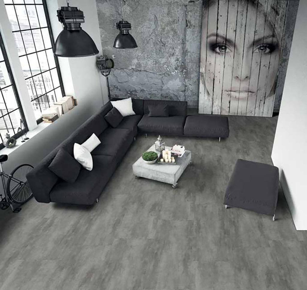 Un grand salon est photo graphié de haut. Canapé gris anthracite, fresque murale avec un portrait de femme, sol vinyle gris souris. Un camaïeu de gris proposé par Udirev