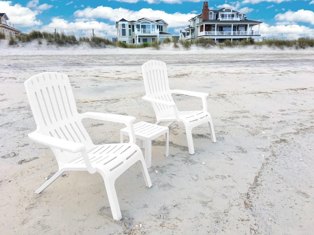 Deux fauteuils Adirondacks blancs sur une plage normande