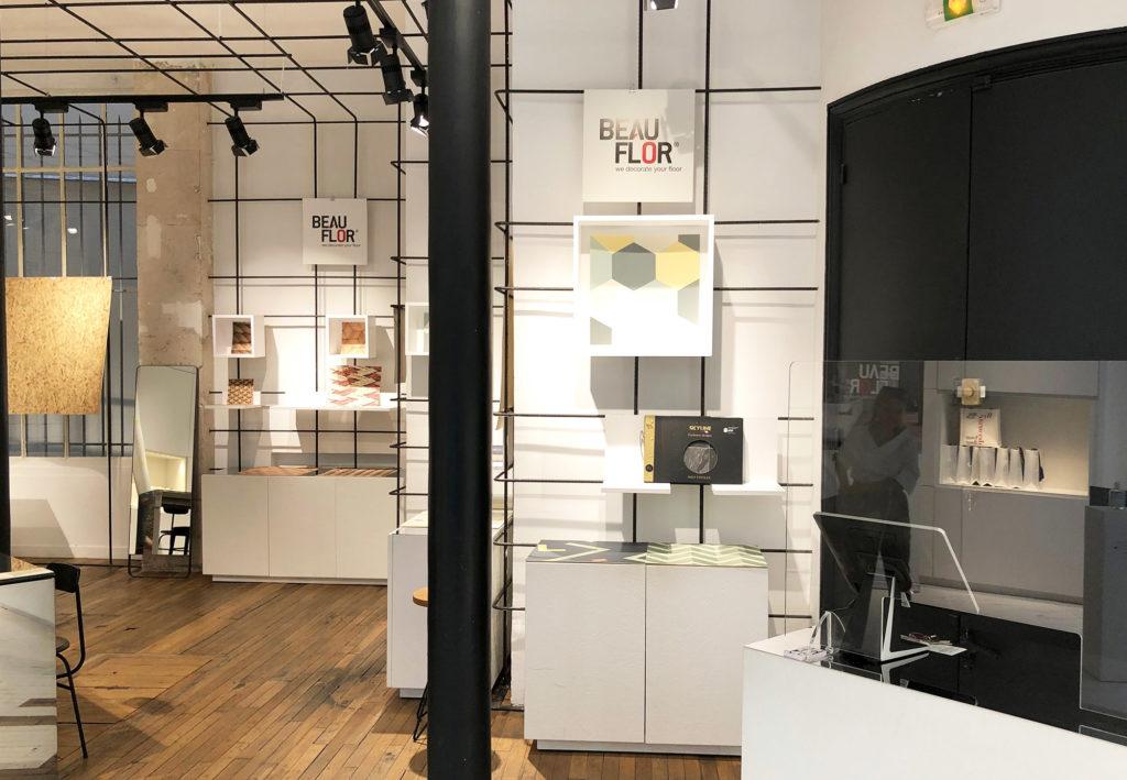 des échantillons de sol vinyle Beauflor sont présentés dans des coffrets blancs accrochés au mur de la galerie