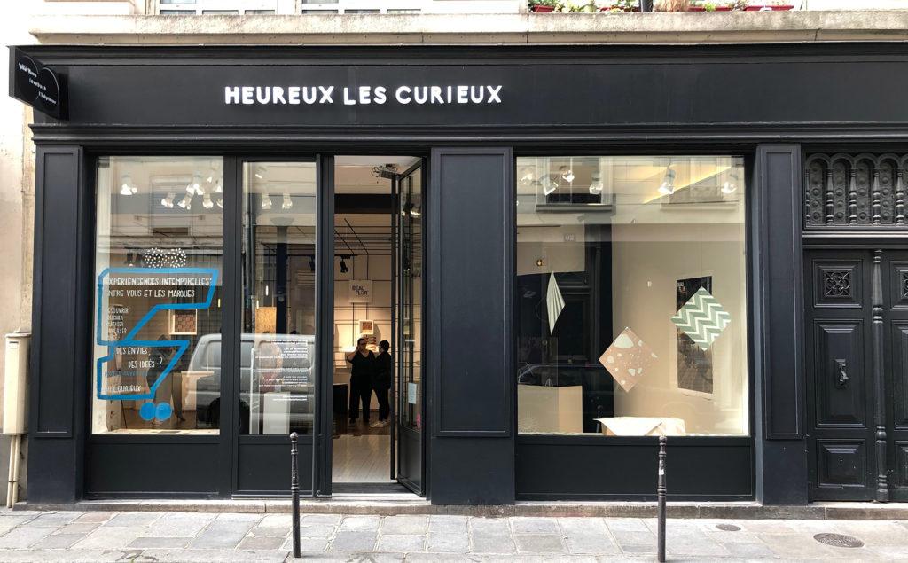la devanture de l'espace Heureux les curieus. Une boutique noire dans le Marais parisien transformé en gallerie