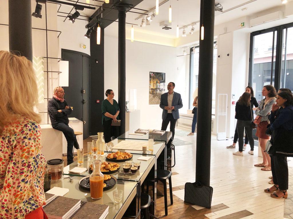 Le responsable prescription Beauflor présente à une assemblée d'architectes le nouveau sol vinyle impression digitale. Ils osnt dans un espace pop up du Marais, debouts autour d'un buffet petit-déjeuner