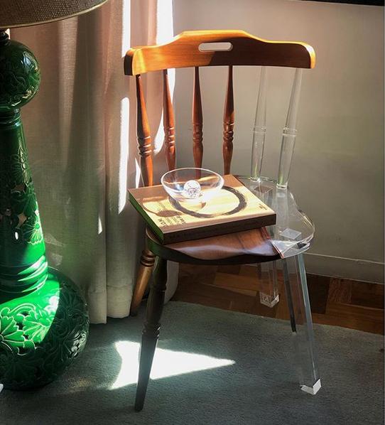 Une chaise rustique en bois dont la partie manquante a été remplacée par une pièce en acrylique transparent. Dessus est posé un petit plateau en bois