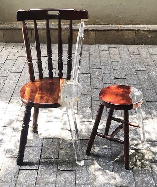 Une chaise rustique et un petit tabouret en boisdont les parties manquantes, brisées ont été remplacées par des pi-èces en acrylique