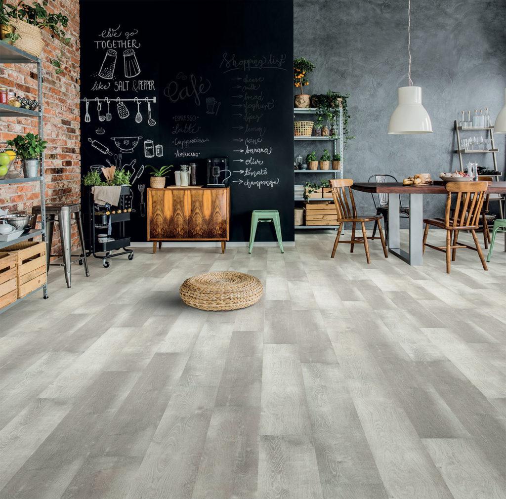 une superbe cuisine devient une pièce à vivre agréable grâce au sol acoustique UDIREV. Au fond le mur a été transformé en une immense ardoise avec de la peinture tableau