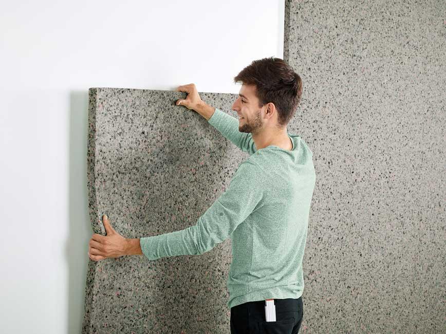 un jeune homme colle un panneau acoustique Silentwall sur un mur en plâtre