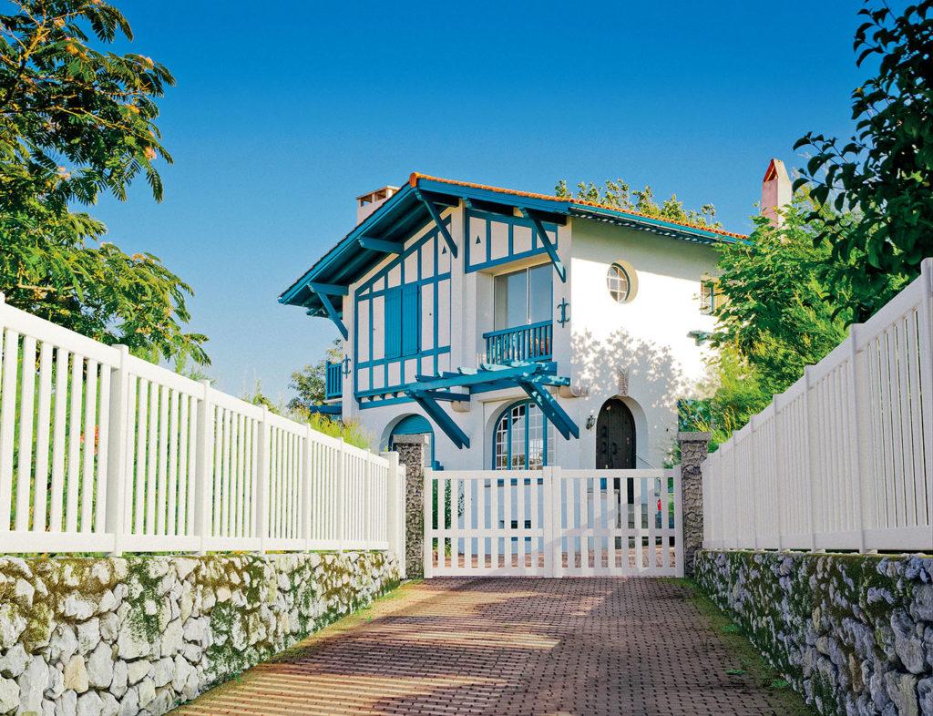 Une maison de style basque aux volets bleus. Elle est fermée par un portail blanc Préfalu