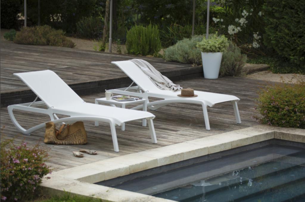 Deux bains de soleil blancs au bord d'une piscine. Un chapeau de paille et un cabas sont posés